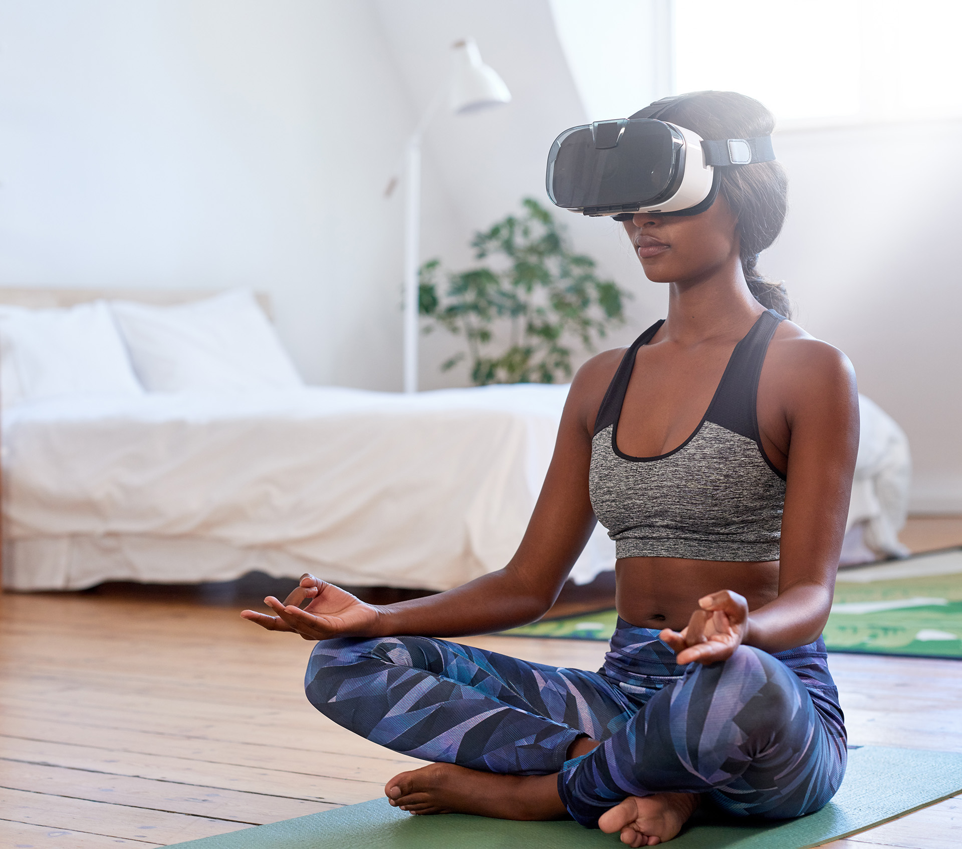 Woman meditating at home with VR goggles